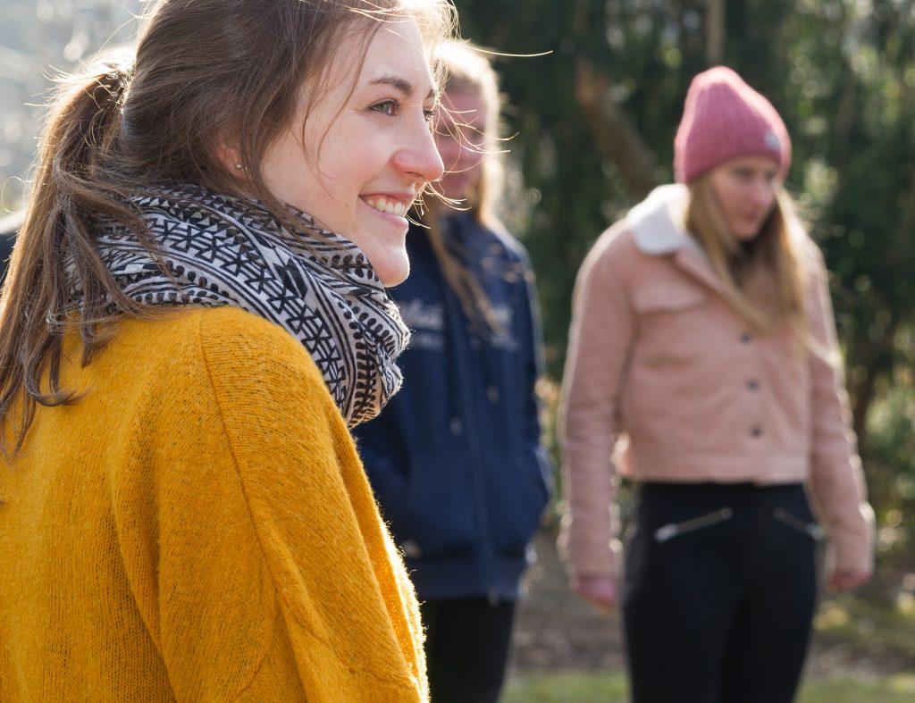 Lächelnde Jugendliche in einer Gruppe im Freien