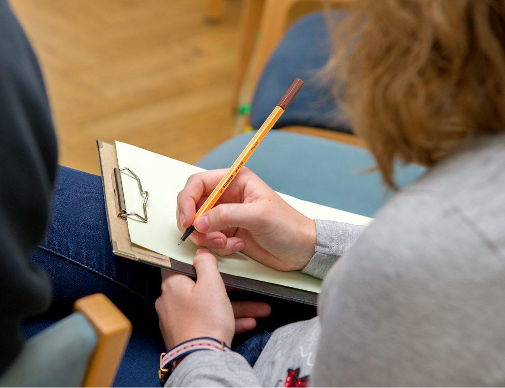 Jugendliche mit Schreibbrett und Stift in der Hand